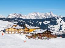 Den sluttande lutningen och apres skidar bergkojan med restaurangterrassen i den Saalbach Hinterglemm Leogang vintersemesterorten Royaltyfri Bild