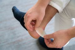 Den smärtsamma hälsåret mans på fot som orsakas av nya skor Mans händer royaltyfria bilder