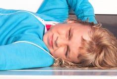 Den små blonda flickan i tillfällig sport outwear lies royaltyfria foton