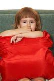Den små flickan med ett rött kudder Arkivfoton