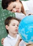 Den små schoolboyen använder det terrestrial jordklotet royaltyfri fotografi