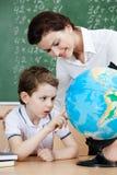 Den små schoolboyen ser det terrestrial jordklotet royaltyfria bilder
