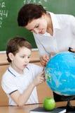 Den små schoolboyen studerar geografi arkivfoto