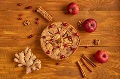 Den smakliga äppelpajen med nya röda tranbär och valnötter dekorerade med tre äpplen, ingefäran, kanel Precis dragen tillbaka äpp Fotografering för Bildbyråer