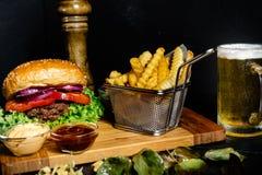 Den smakliga nötkötthamburgaren tjänade som med småfiskar och grönsallat på träbräde på den lokala baren Royaltyfri Bild