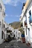 Den smala gatan med en mosaik i mitt, blått lägger in och sparkcyklar, Frigiliana - spansk vit by Andalusia Arkivbild