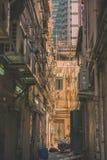 Den smala gatan mellan skyskrapor, en port, vad döljas från offentliga ögon, ett rör av kommunikationen av vattenförsörjning och  arkivfoton