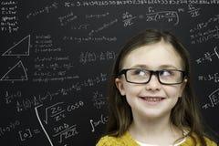 Den smart ung flicka stod infront av en blackboard Royaltyfri Bild