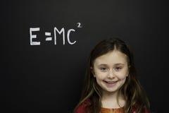 Den smart ung flicka stod infront av en blackboard Royaltyfri Foto