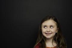Den smart ung flicka stod infront av en blackboard Arkivbild