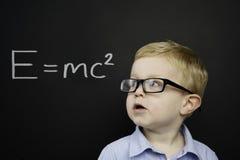 Den smart unga pojken stod framme av en blackboard Arkivbilder