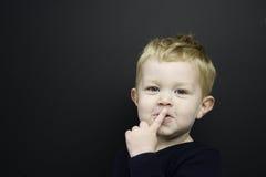 Den smart unga pojken stod infront av en blackboard Arkivfoto