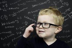 Den smart unga pojken stod infront av en blackboard Fotografering för Bildbyråer