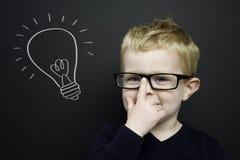 Den smart unga pojken stod infront av en blackboard Arkivbild
