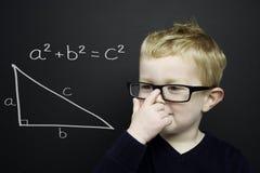 Den smart unga pojken stod infront av en blackboard Arkivfoton