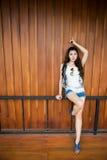 Den smarta asiatiska flickan poserar mot träväggen Royaltyfria Foton