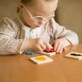 Den smarta flickan med Down Syndrome samlar pussel fotografering för bildbyråer