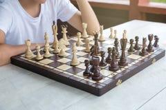 Den smarta, gulliga unga pojken gör en flyttning på schackbrädet Utbildningsbegrepp, intellektuell lek, utbildning arkivfoton