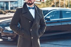 Den smarta mannen i lag st?r n?ra hans nya bil arkivfoto