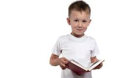 Den smarta pojken och öppnar boken som isoleras på en vit bakgrund Royaltyfri Bild