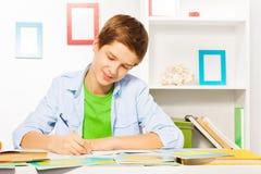 Den smarta stiliga pojken skriver i lärobok, gör läxa royaltyfri fotografi