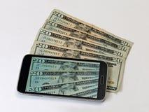 Den smarta telefonen fördjupa fläktade 20 dollarräkningar royaltyfri foto