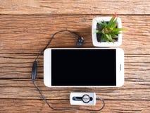 Den smarta telefonen och öron pluggar på träbakgrund Fotografering för Bildbyråer