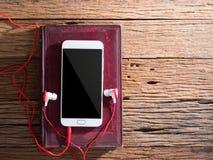 Den smarta telefonen och öron pluggar på träbakgrund Arkivfoton