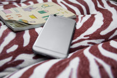 Den smarta telefonen och en anteckningsbok lägger på kramkudden Fotografering för Bildbyråer