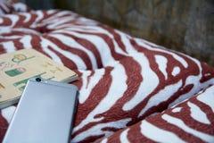 Den smarta telefonen och ett anteckningsbokställe på en kram kudde Royaltyfri Fotografi
