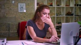 Den smarta trevliga funktionsdugliga caucasianen som är kvinnlig med rött hår, gäspar, medan sitta nära bärbara datorn och kontor lager videofilmer