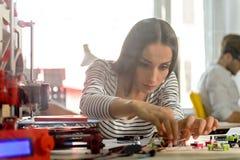 Den smarta unga kvinnan iscensätter tredimensionell printing Royaltyfria Bilder