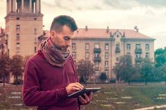 Den smarta unga mannen arbetar på minnestavladatoren utomhus i stads- offentligt utrymme fotografering för bildbyråer