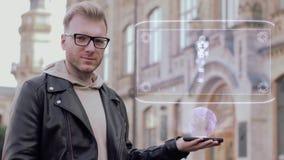 Den smarta unga mannen med exponeringsglas visar ett begreppsmässigt hologram den enkla cyborgen lager videofilmer