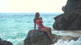 Den Smilling kvinnan som sitter på, vaggar på stranden på havsvåg- och klippalandskap Härlig kvinna i baddräkt på sommarstranden lager videofilmer