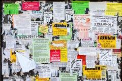 Den smutsiga anslagstavlan som fylls med papper, märker på rysslangua Royaltyfri Bild