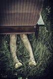 Den smutsiga kvinnlign lägger benen på ryggen klibba ut från under en fåtölj i ett fält, ovanligt begrepp för mörkt lynne Royaltyfria Foton