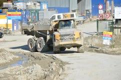 Den smutsiga tunga Volvo dumperen laddade vaggar förbi inflyttningarbetsplatsen Det finns slovak huvudvägen märkt D1 under konstr royaltyfri fotografi
