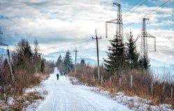 Den snöig vägen bland berg och hög spänning fodrar Arkivfoto
