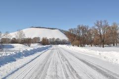 Den snöig vägen och kullen Fotografering för Bildbyråer