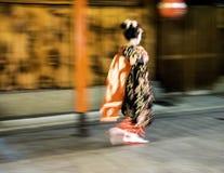 Den snabba japanska geishaen går under regnig natt på Gion District i Kyotom Japan Royaltyfria Foton