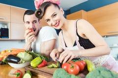 Den snarlika lata mannen håller ögonen på hans fru att förbereda maten royaltyfria foton