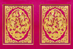 Den sned guld- draken dekorerade på röd trädörr Arkivfoton