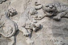 Den sned stenen av den kinesiska templet och tigerstatyn Arkivfoto