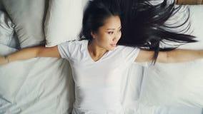 Den snygga asiatiska brunetten i den vita T-tröja ligger ner på bekväm säng med vit linne och trycker på hennes hår lager videofilmer