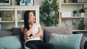 Den snygga asiatiska flickan talar på mobiltelefonen som ler och skrattar sammanträde på soffan i härlig modern lägenhet arkivfilmer