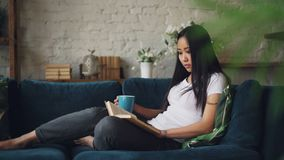 Den snygga asiatiska kvinnan är läseboken som tycker om modernt litteratursammanträde på den hemmastadda hållande kopp te för sof lager videofilmer