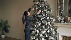 Den snygga brunetten dekorerar gran-trädet med härliga bollar och ljus som tycker om festlig aktivitet på vinter arkivfilmer