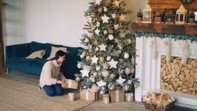 Den snygga flickan i varm tröja kommer med gåvaaskar till julgranen, sätter dem under gran-träd och ler därefter lager videofilmer
