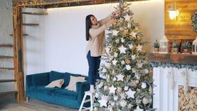 Den snygga kvinnan dekorerar gran-trädet för julferier som sätter garneringbollar och stjärnor på filialer arkivfilmer